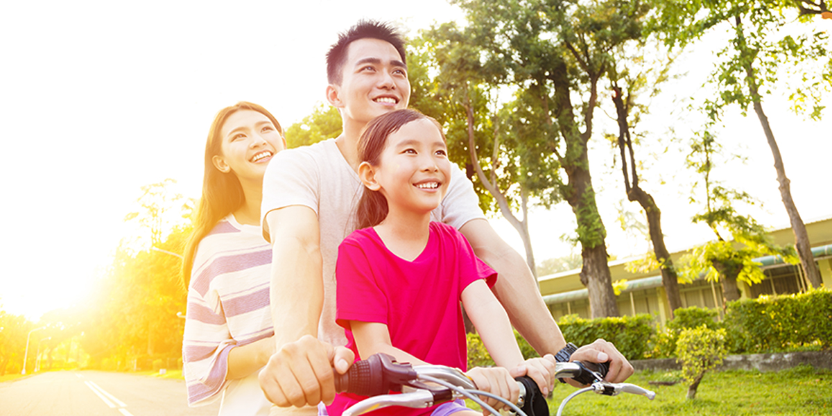 Healthy and happy family taking a bike ride together enjoying the sunshine